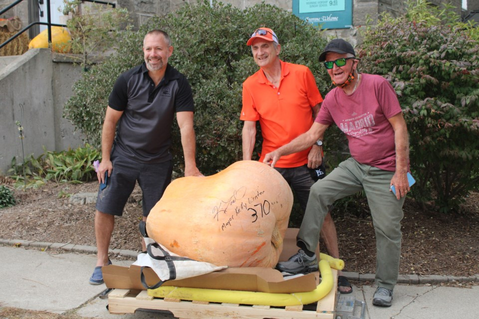 (Left to right) Centre Wellington mayor Kelly Linton with his father Bob Linton and father-in-law John VanDriel. Linton's pumpkin weighed in at 370 lbs and he credits his father and father-in-law for doing the bulk of the work. Keegan Kozolanka/GuelphToday