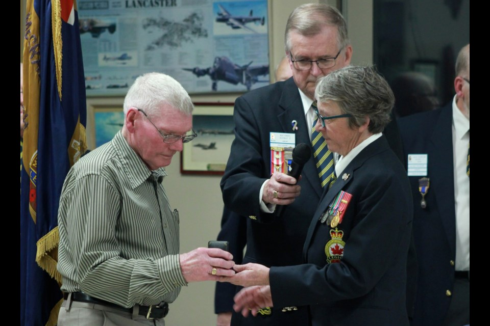 Susan Giebel hands the war medal to George Cook. Anam Khan/GuelphToday