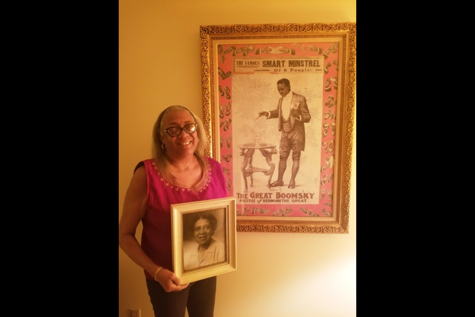 Karen McLaurin poses with images of her grandparents, Blanche Stoutley Willis, and magician Isaac Willis, the Great Boomsky.