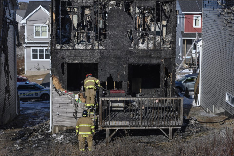 Firefighters investigate following a house fire in the Spryfield community in Halifax on Tuesday, February 19, 2019. (Darren Calabrese/The Canadian Press)