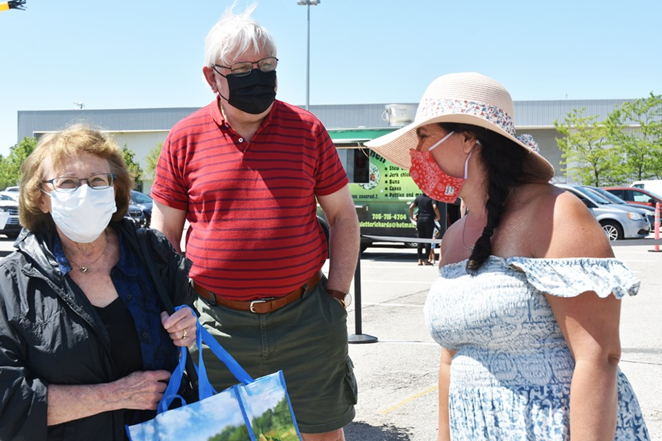 Innisfil Farmers' Market manager Jaime Grant, right, screens visitors to the market, at the Innisfil Rec Complex.
