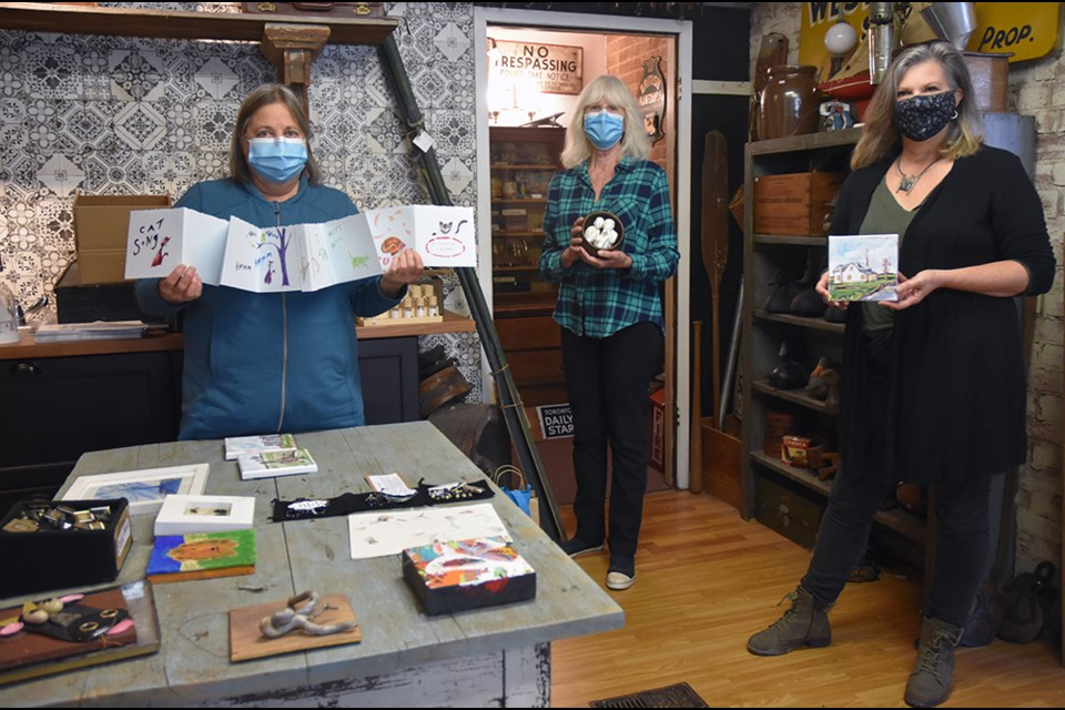 From left, artists Christina Luck, Gail Esau and Maggie Grace with their miniature 6 in. by 6 in. works, at Halliday House & Co. in Cookstown. Miriam King for InnisfilToday