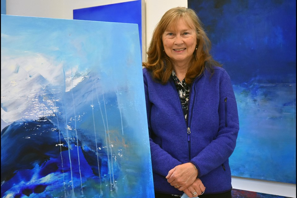 Artist Janet Read in her Innisfil studio with paintings from her solo show, High Arctic Light.