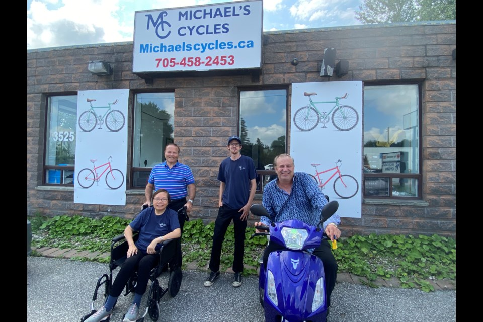 Michael Menzies with wife Iris, along with shop employee Aric Howser and friend Scott Hill.