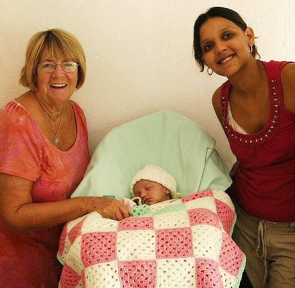 Marilyn Sehn, owner of The Knotty Crow and The Baby Crow on Etsy, posing with a local and her new baby in Puerta Vallarta, Mexico with a crochet baby blanket she made for them. /Photo Submitted