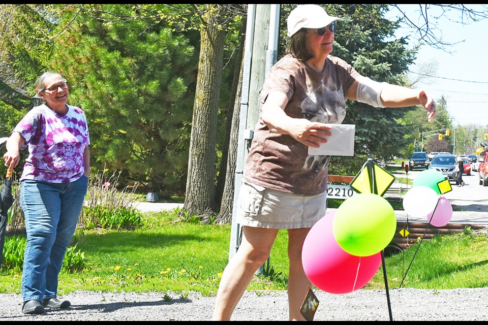 Ginny Clements, right, shares an 'air hug' during the birthday parade, as Patty McLaughlin looks on - always social distancing. Miriam King/Innisfil Today