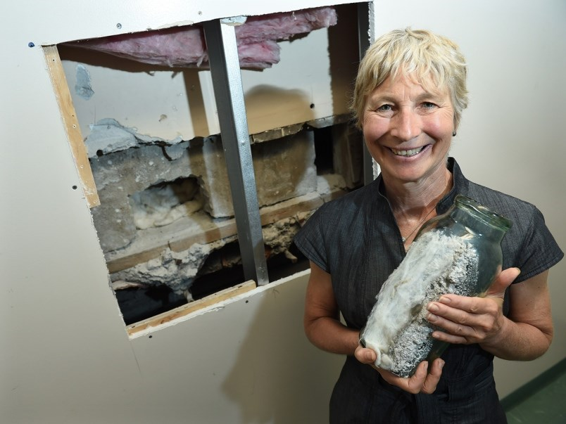 Shaughnessy elementary principal Janet Souther holds the emptied 100-year-old time capsule in front of where it was extracted. (via Dan Toulgoet)
