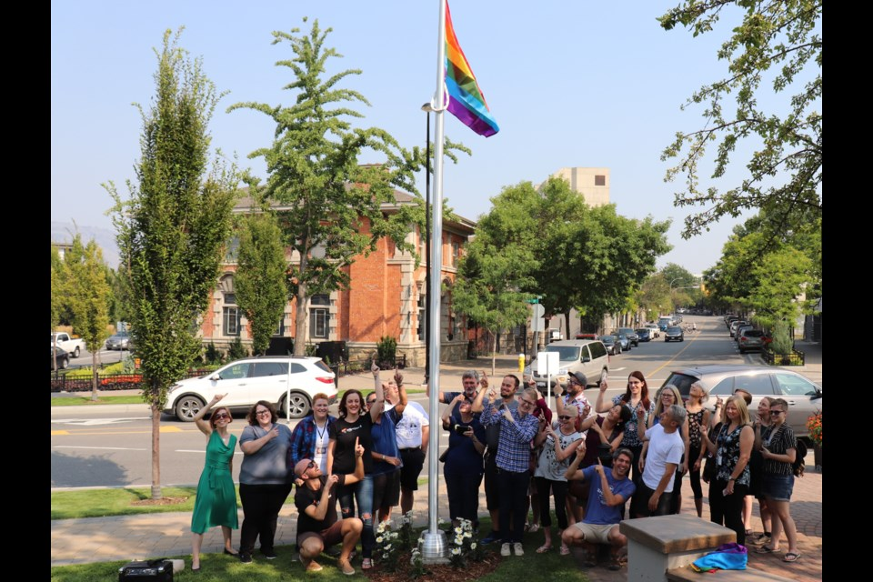 Members of Kamloops Pride, the LGBTQ2S+ community, allies and city councillors pose in front of the flag and pole. (via Brendan Kergin)