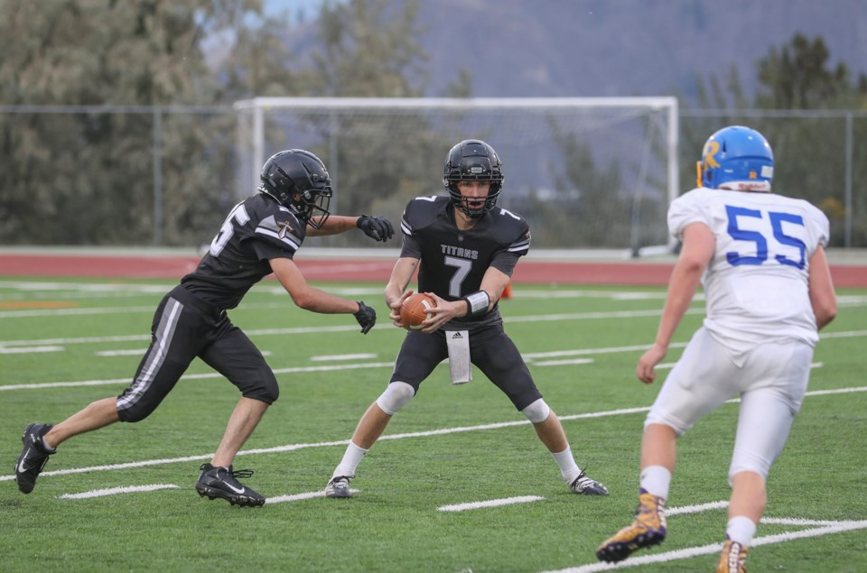 1 QB Jesse Peters  hands off to Jakob Kies (25) who also made brilliant defensive plays in the game while Rutland's Elliot Vander Horst (56) homes in_7533