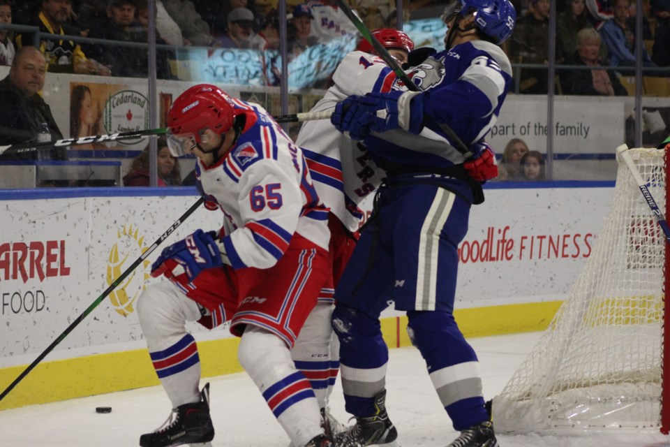 Kitchener Rangers forward Riley Damiani gets tangled up with Sudbury's Quinton Byfield behind the Kitchener net.  Mark Pare/KitchenerToday