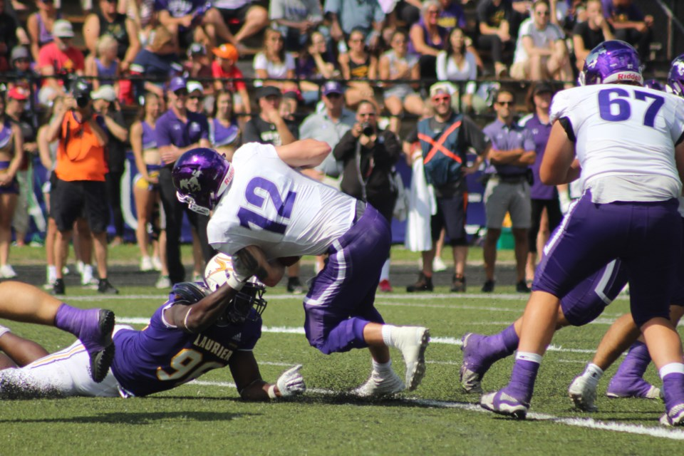Laurier DT Sam Acheampong (96) is able to pull down Western QB Merchant for a sack during an OUA regular season game.  Mark Pare/KitchenerToday