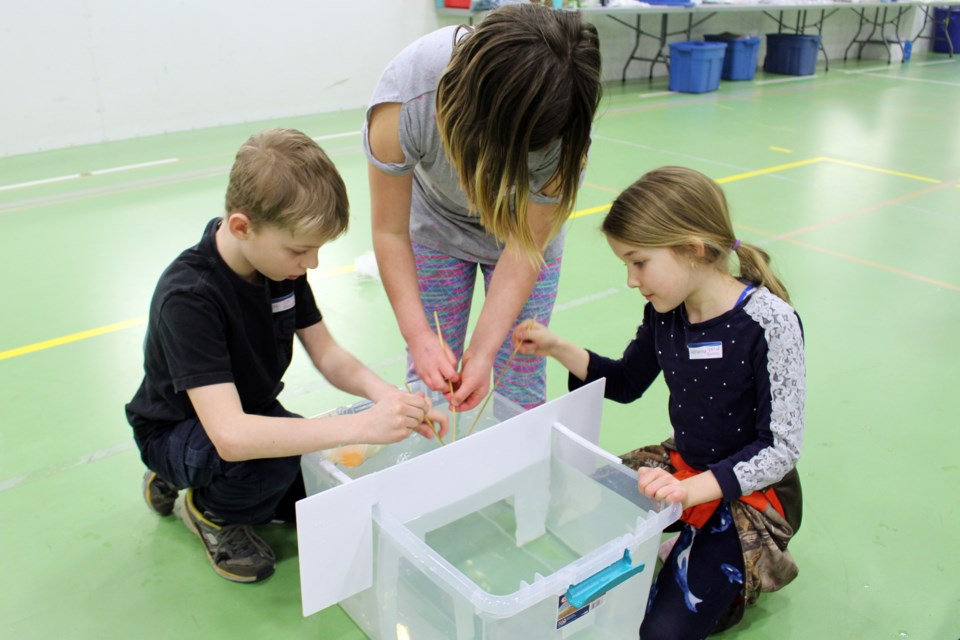 Groups worked together to create a vessel that would transport ping pong balls underwater. (left to right) Eric Vadnais, 10, Callie Maheden, 10, and Adrianna Paplia, 8. Photo by Robynne Henry.