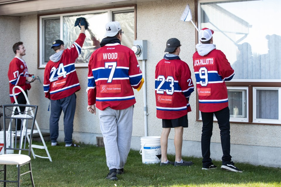 A group of Jr. B hockey players clean windows at Heritage Homes, in St. Paul, Oct. 6. Janice Huser photo.