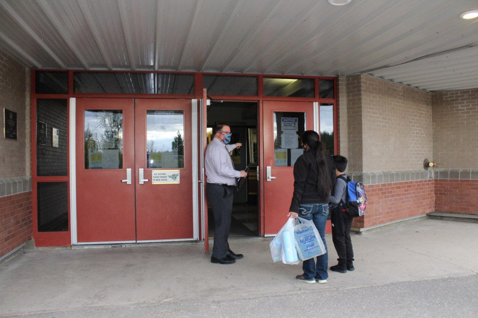 Aurora Middle School Principal Conal Donovan welcomes a young student and his mom to the first day of classes. Parents were encouraged to bring new middle school students into the school to make the transition from elementary school a little easier.    Image: Rob McKinley