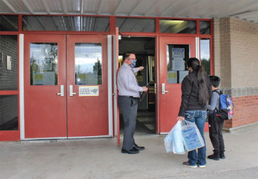 Aurora Middle School principal Conal Donovan welcomes students and families back to school in this file photo from the start of September. School officials announced Tuesday night that the school is tied to an active case of COVID 19.       File Rob McKinley