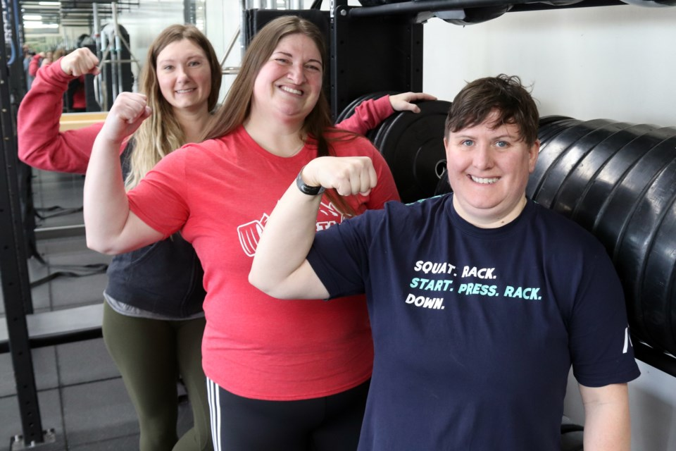 Local powerlifters Janine Hebert (centre) and Carole Vachon (right) pose for a photo with their coach Jessica Brennan (left) after sharing their experience at CPU Nationals. Photo by Meagan MacEachern.