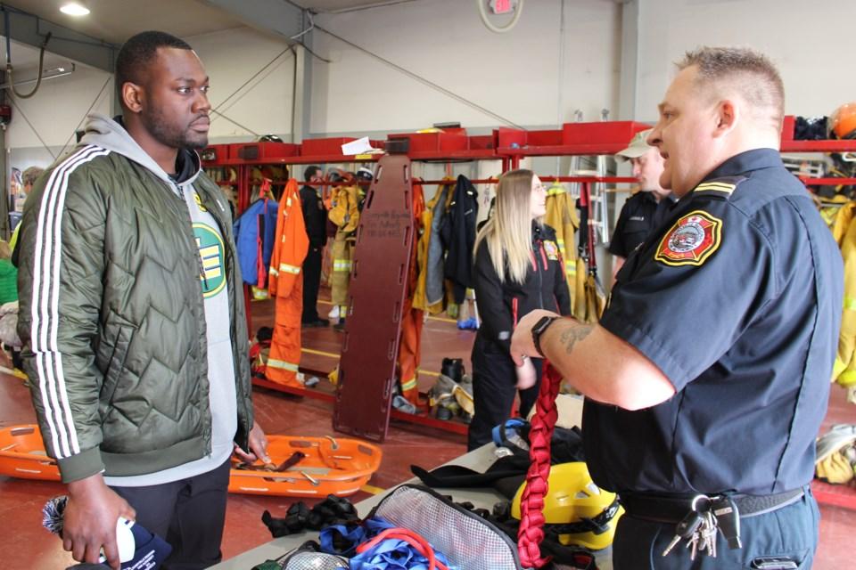 Edmonton Eskimo defensive-end Kwaku Boateng (left) listens to Bonnyville Regional Fire Authority regional training and fire prevention officer Capt. Dwayne Ethier. Photo by Robynne Henry.