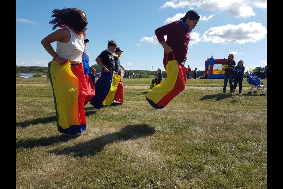 Older kids attending the Mission picnic jumped at the chance to compete in a sack race.