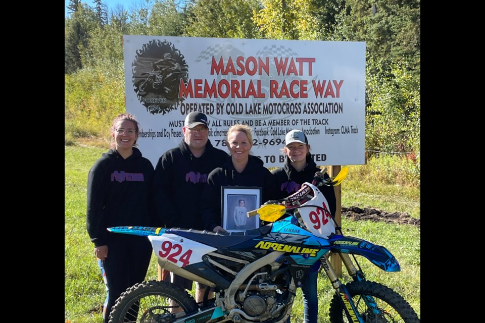 The Watt family, parents Trevor and Tara, and siblings Madi and McKenna pose with Mason's bike in front of the Mason Watt Memorial Race Way sign in Cold Lake.