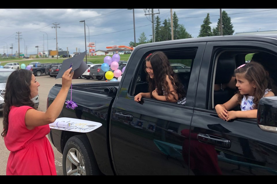 Lac La Biche's Vera M . Welsh Kindergarten teacher Charissa Delaire has a grad cap and cheers for Neda Othman who is going into Grade 1. Neda, her sister Saja — who will be entering playschool —  and her parents, were part of last Tuesday's 'wave-through' at the school.