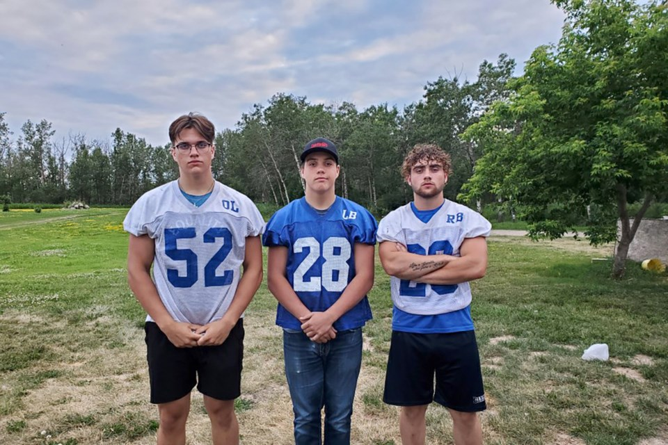 (Left to right) Bonnyville football players and brothers Connor and Liam Critch both made the Football Alberta provincial teams. Here, they post for a photo with their older brother, Duncan. / Photo supplied
