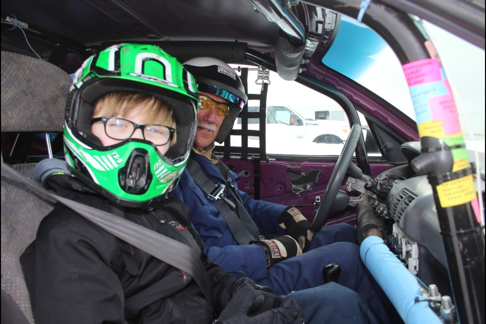 Staples behind the wheel of his ice racing Neon with one of several 'passengers' who took part in the fundraising ride-along during last year's races.  The ride-along program will roll again this year.