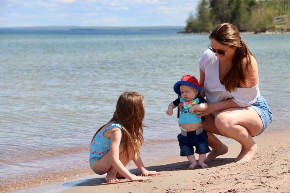 Families flocked to Cold Lake's shores over the weekend to soak up some sun. Here, Shania Frost and her six-year-old daughter Hannah and three-month-old son Axel enjoy the warm weather at Kinosoo Beach. Meagan MacEachern Photo
