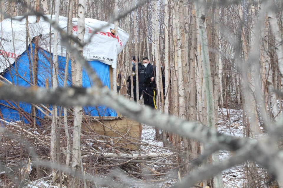 A Lac La Biche RCMP constable looks across the camp area as police and peace officers discussed the removal and tear-down plan with community advocates and camp leaders.