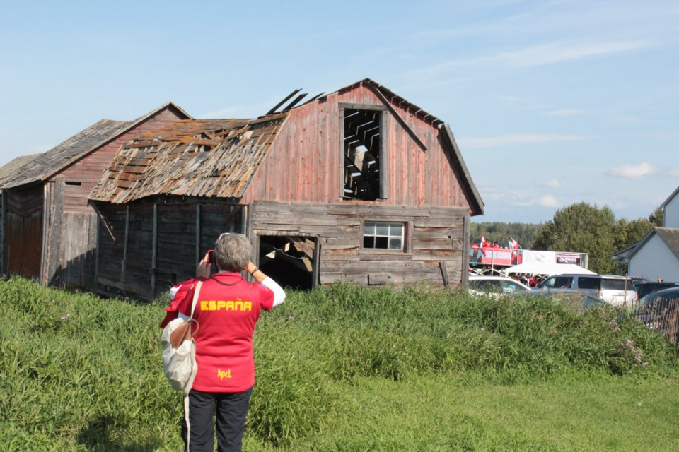A visiting athlete from Spain during the 2019 world archery championships hosted in Lac La Biche County takes a photo of the old barn at the Mission site. The Mission has been the backdrop of Canada Day celebrations and other cultural events for decades.