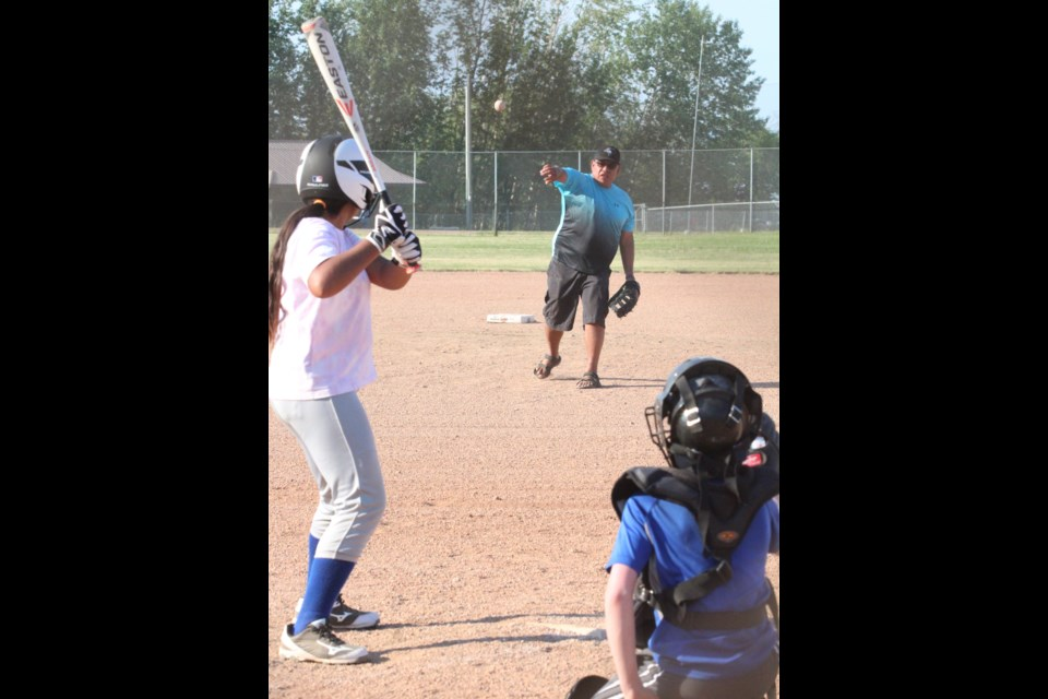 Lac La Biche Minor Ball vice president and U13coach Ryan  Pruden pitches to his daughter as catcher Silas Weening backstops during a practice session on Main 1 last Thursday.