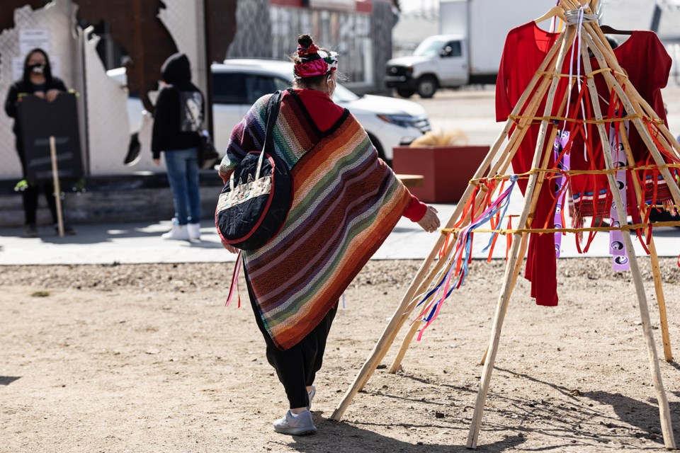 In small groups, those in attendance at an event on Wednesday at the park on main street in St. Paul tied red ribbons to a tipi, in honour of MMIWG.