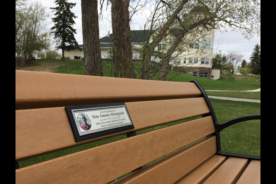 A memorial bench and plaque for Sine Abougoush, a local man who passed away in 2019, sits alongside Lac La Biche lake in McArthur Park.