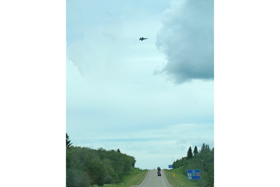 A CF-188 Hornet flies over Highway 28 at the western entrance to Cold Lake. This week the base has been hosting a NORAD-based training event.