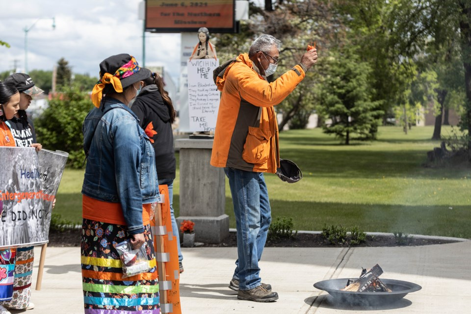 Tobacco ties were placed into a fire, in honour of the 215 children found in unmarked graves in Kamloops.