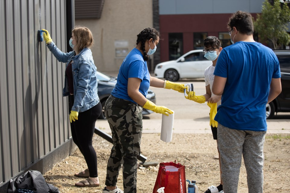 Youth and other community members clean up graffiti on July 22. Janice Huser photo.
