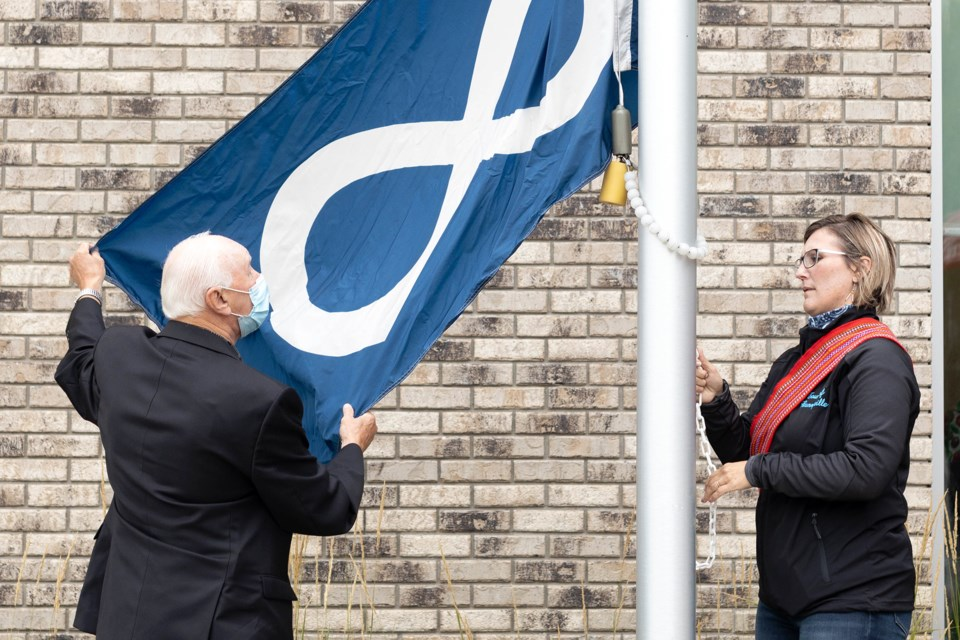 Town of Bonnyville councillors Ray Prevost and Elisa Brosseau lift the Métis flag on Sept. 2 in front of the municipality's townhall.