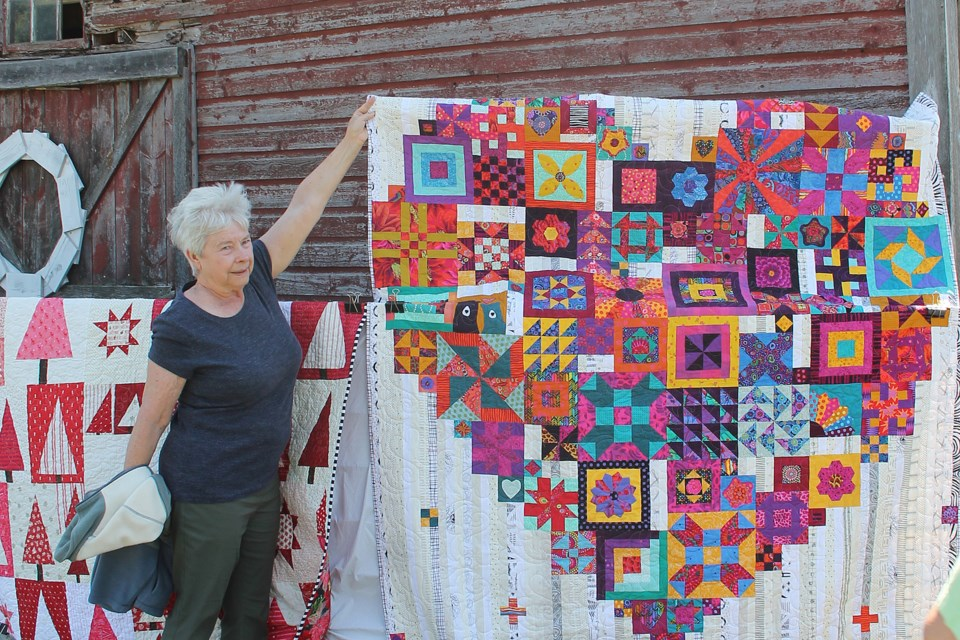 Doris Wilson holds up a corner to help display an outstanding fabric art 'Boho Heart' quilt created by Janice Pritchard and inspired by an Australian designer.
