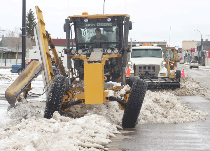 Graders clear slush and snow from 50th Avenue.