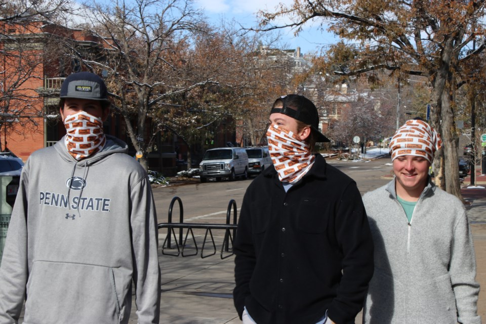 College students Colin Berg (left), Connor Dreher and Brady Bowman stroll through downtown Boulder, Colorado, in mid-November wearing matching neck gaiters. Some research suggests the thin material used in gaiters does not block as much of the coronavirus as cloth face masks do, even when worn correctly, doubled over and covering the nose and mouth. (Markian Hawryluk/KHN)