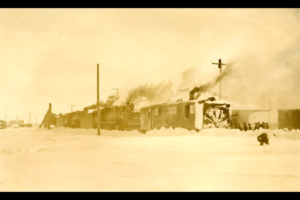 A postcard depicting a train-mounted plow clearing snow off the railroad tracks at 1st & Main in 1913