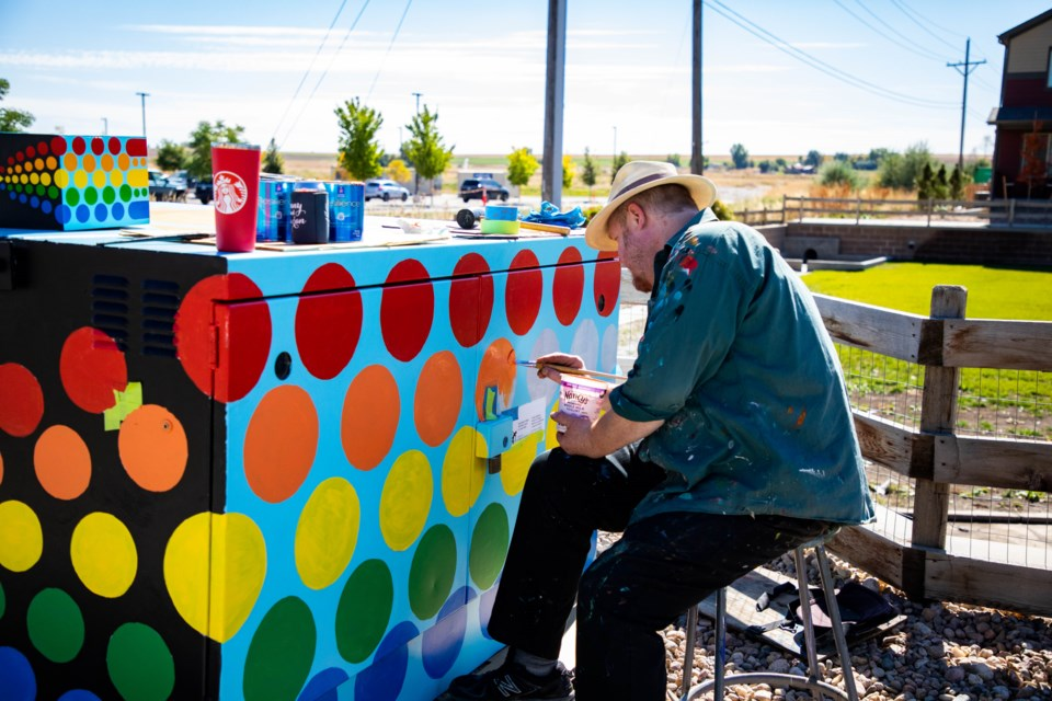 Evan Colbert working on his Rainbow Machine outside the Innovation Center