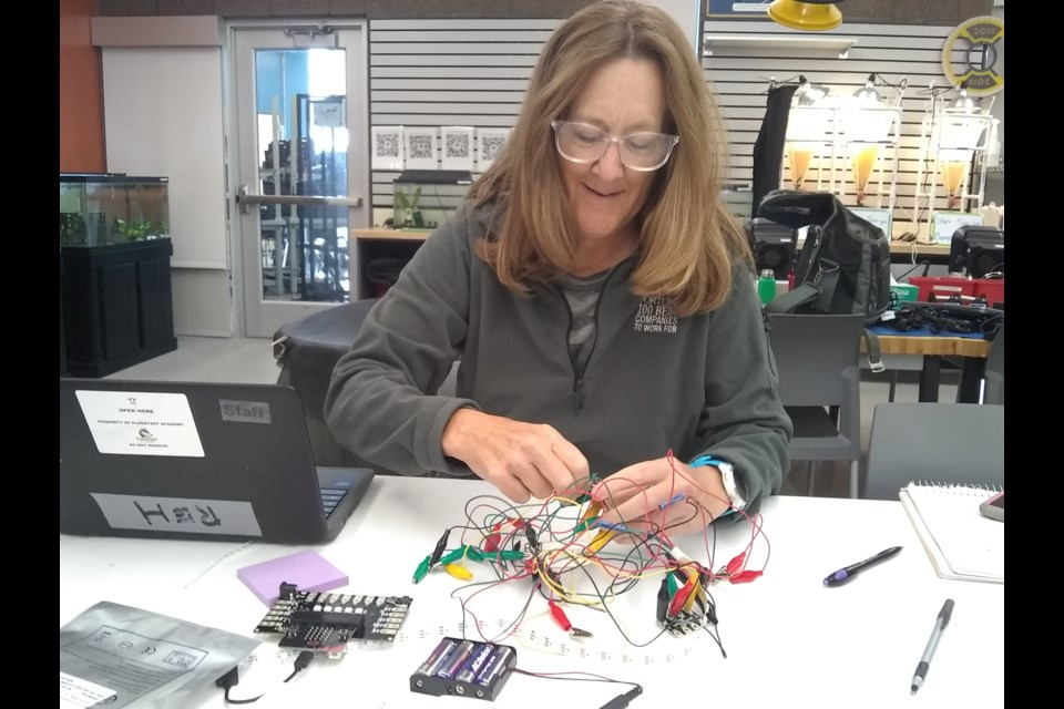 Terri Reh, middle school science/robotics teacher at Flagstaff Academy, works on a data sensor hub (DaSH) board for her classroom.