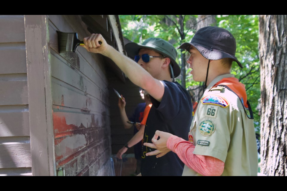 Erik Yoho (right) instructs his fellow troop members as they paint the exterior of the Hover Home's garden shed. (Photo by Ben Berman)