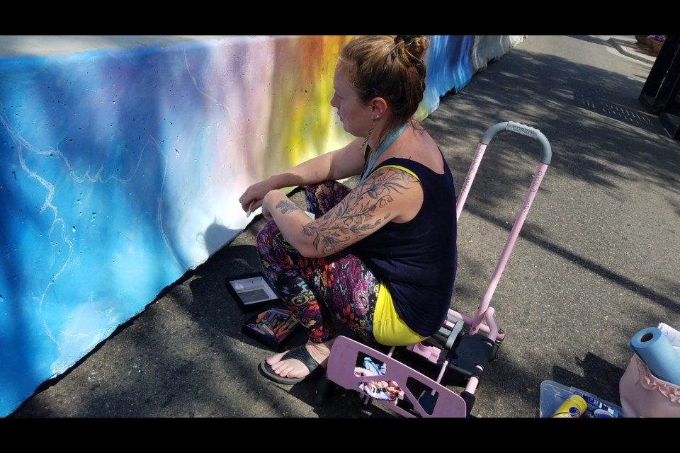 Joyanna Rose Gittings, owner of Obra Arts Studio, paints a section of the barricades along Main Street to make the area look less industrial and to attract more people downtown.  (Photo by Monte Whaley)
