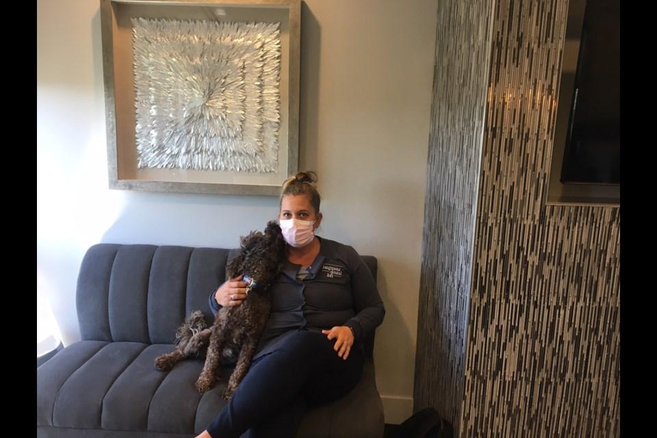 Dr. Adrienne Hedrick gets some affection from Bentley at Longmont Dental Loft on July 1, 2020. (Photo by Julie Baxter)