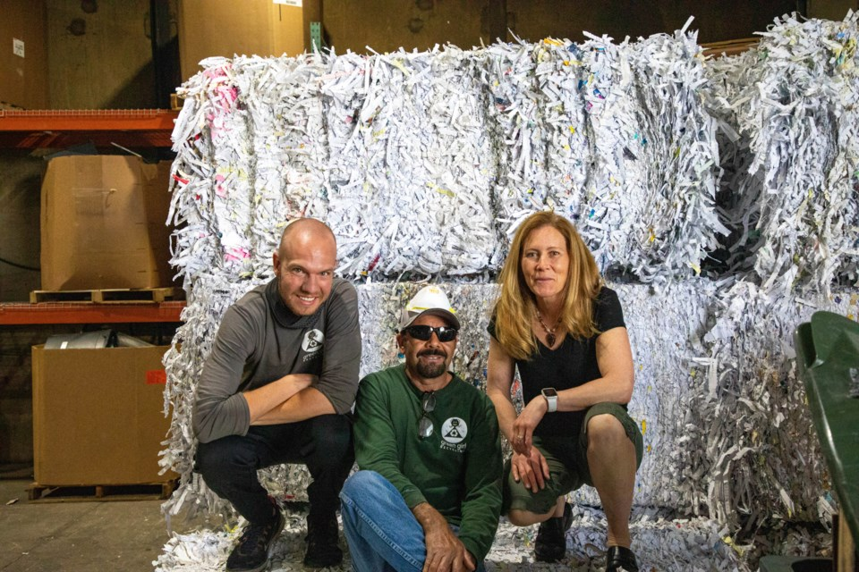 (L to R) Operations manager Brandon Wilkes, warehouse manager Jesus Medina and Green Girl owner Bridget Johnson pose on bales of shredded paper.