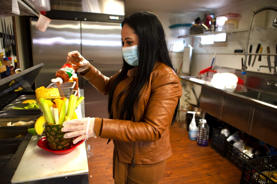 Haydee Caraveo Vasquez, owner of Oasis Fresh Fruit and More, makes one of the restaurant's signature dishes Pina Locuaz, a large fruit assortment in a pineapple, on March 30. Photo by Ali Mai   ali.mai.journo@gmail.com