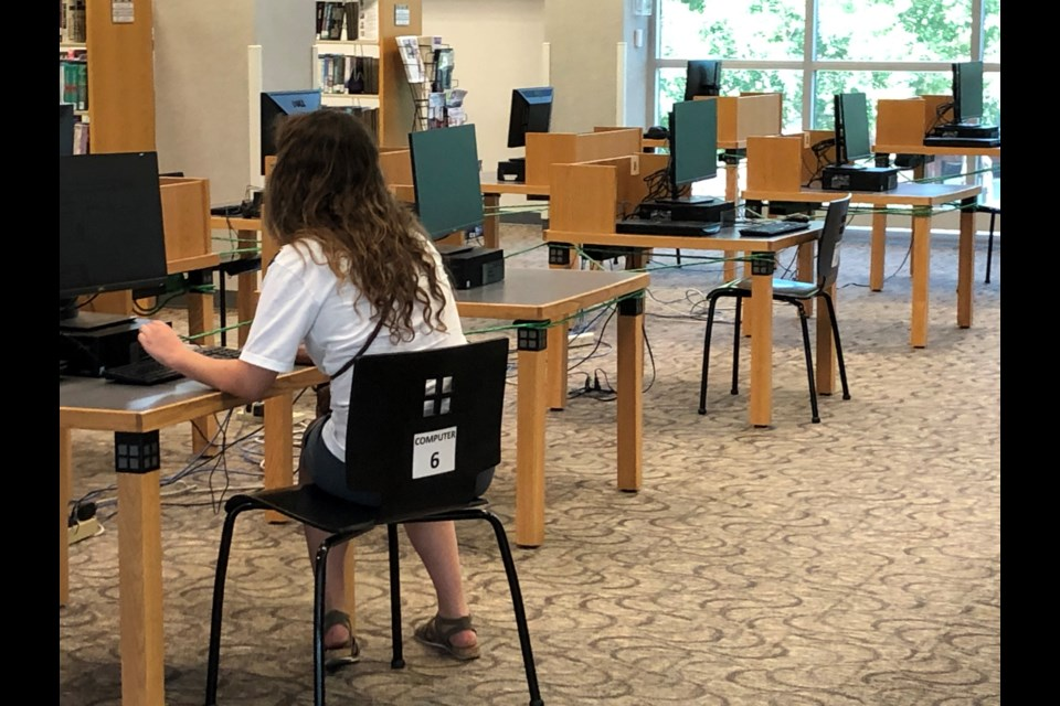 A patron uses a computer at the Longmont library on July 23, 2020, which was its reopening day after being closed in response to the coronavirus pandemic. (Photo by Macie May)