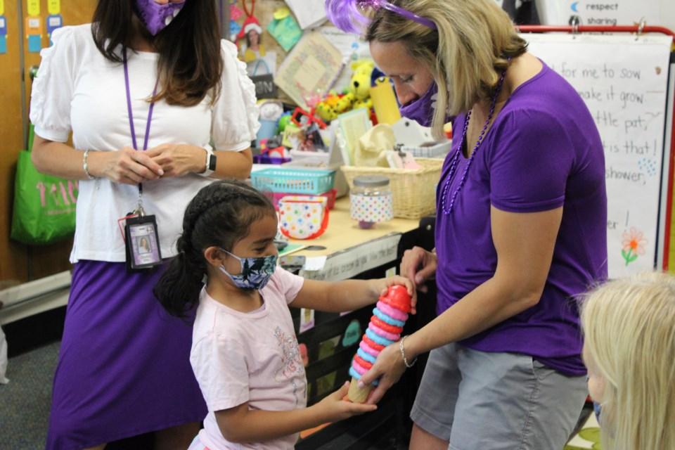 Principal Audrey Seybold listens as preschool student builds an ice cream pattern