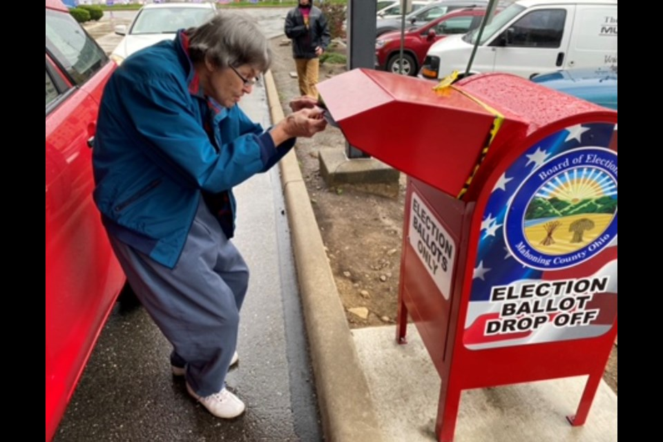 Cheryl Elliott of Boardman drops her completed absentee ballot into the drop box outside the Mahoning County Board of Elections. (Jess Hardin | Mahoning Matters)